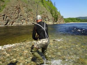 рыбак ловит рыбу на быстром течении