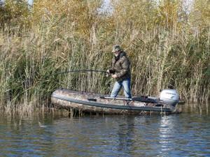 рыбак в лодке ловит щуку