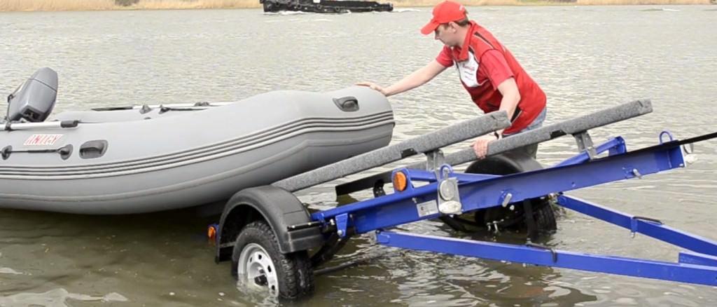 Спускают в воду лодку с прицепа