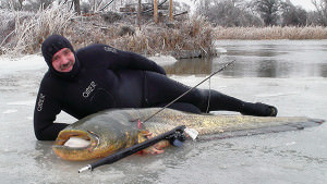 Мужчина рядом с пойманной рыбой