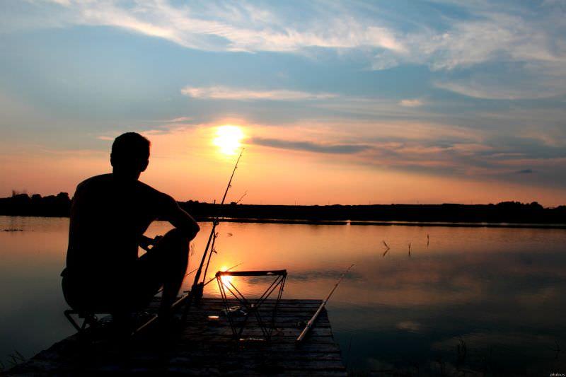 Мужчина ловит рыбу на берегу